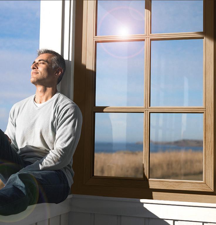 Man sitting on window sill of sun porch, eyes closed